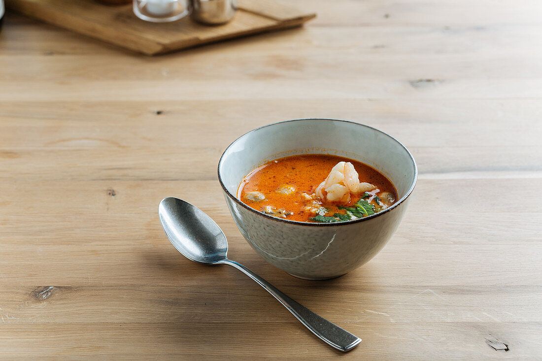 Spicy soup delicacy with shrimps and greenery in ceramic bowl on table with spoon