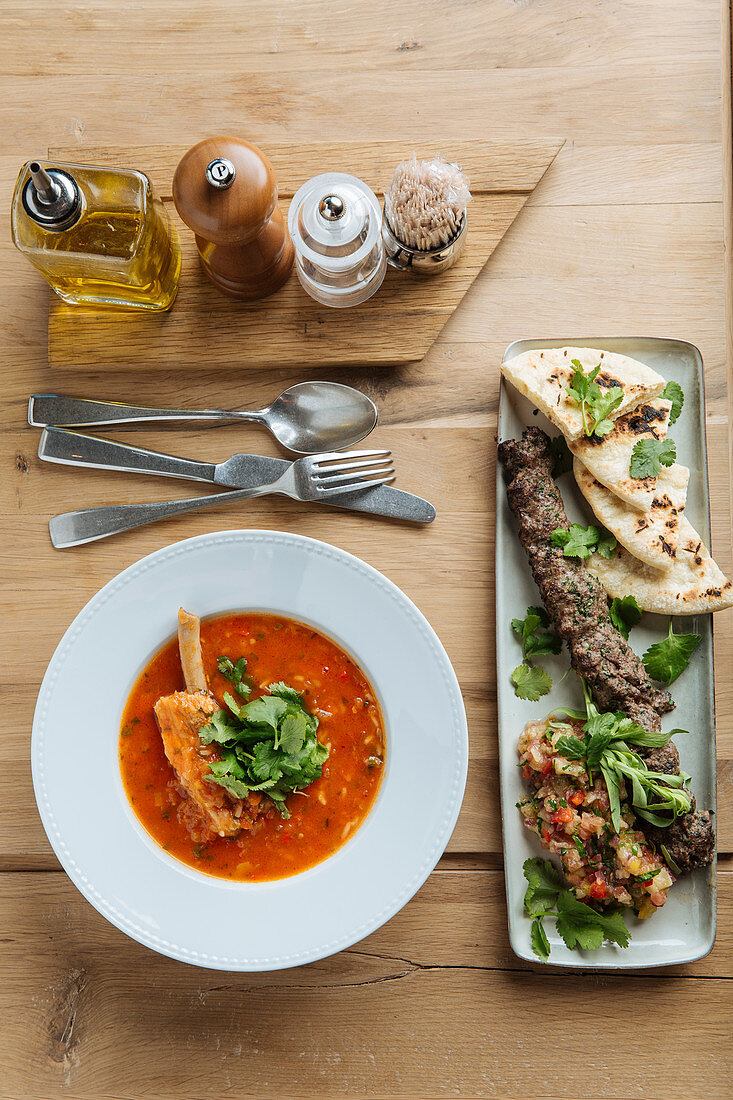 Red soup with meat and fresh herbs with kebab and flat bread