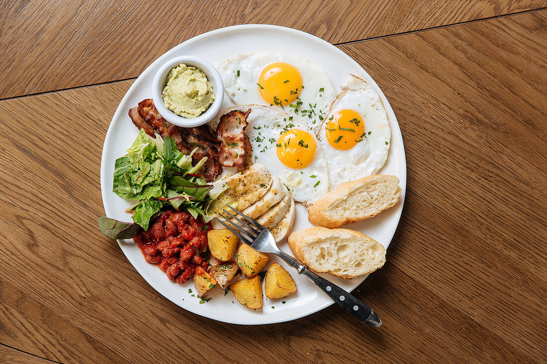 English breakfast with fried eggs and bacon with toasts and vegetables