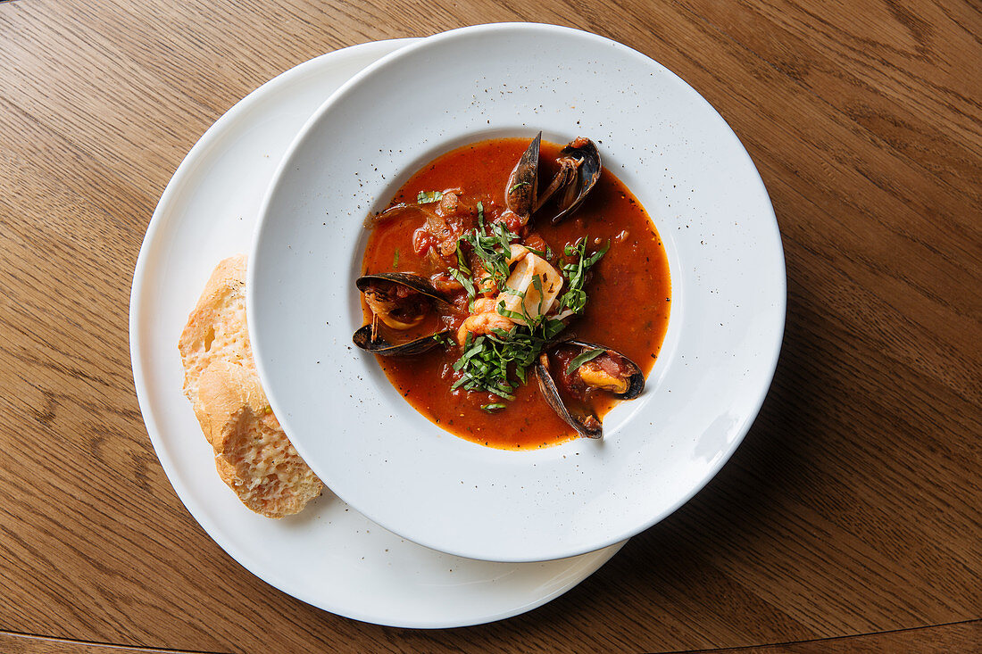 Plate with spicy tomato soup, black mussels and seafood with chopped greens