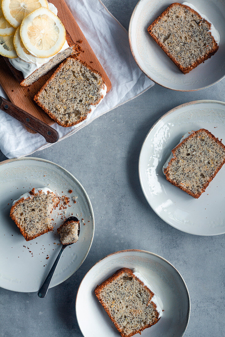 Pieces of lemon and poppy seeds cake served on white plates