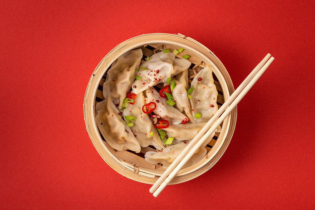Traditional Chinese steamed dumplings in bamboo steamer with wooden chopsticks
