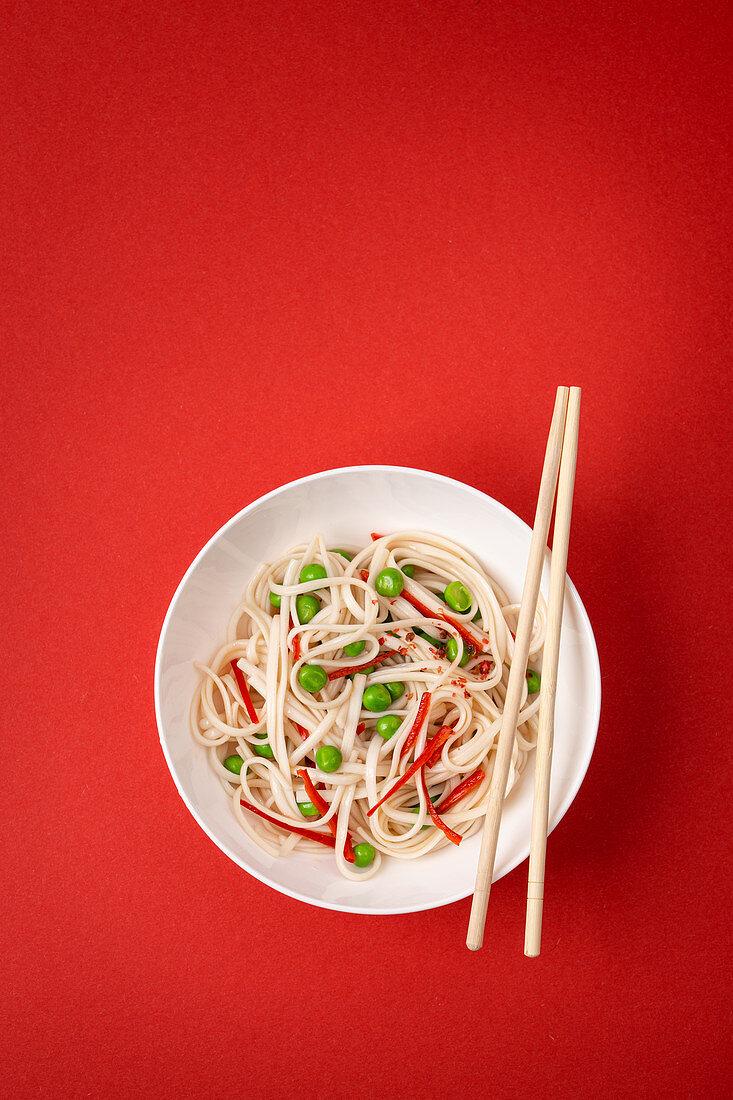 Asianudeln mit Gemüse, Erbsen und rotem Paprika
