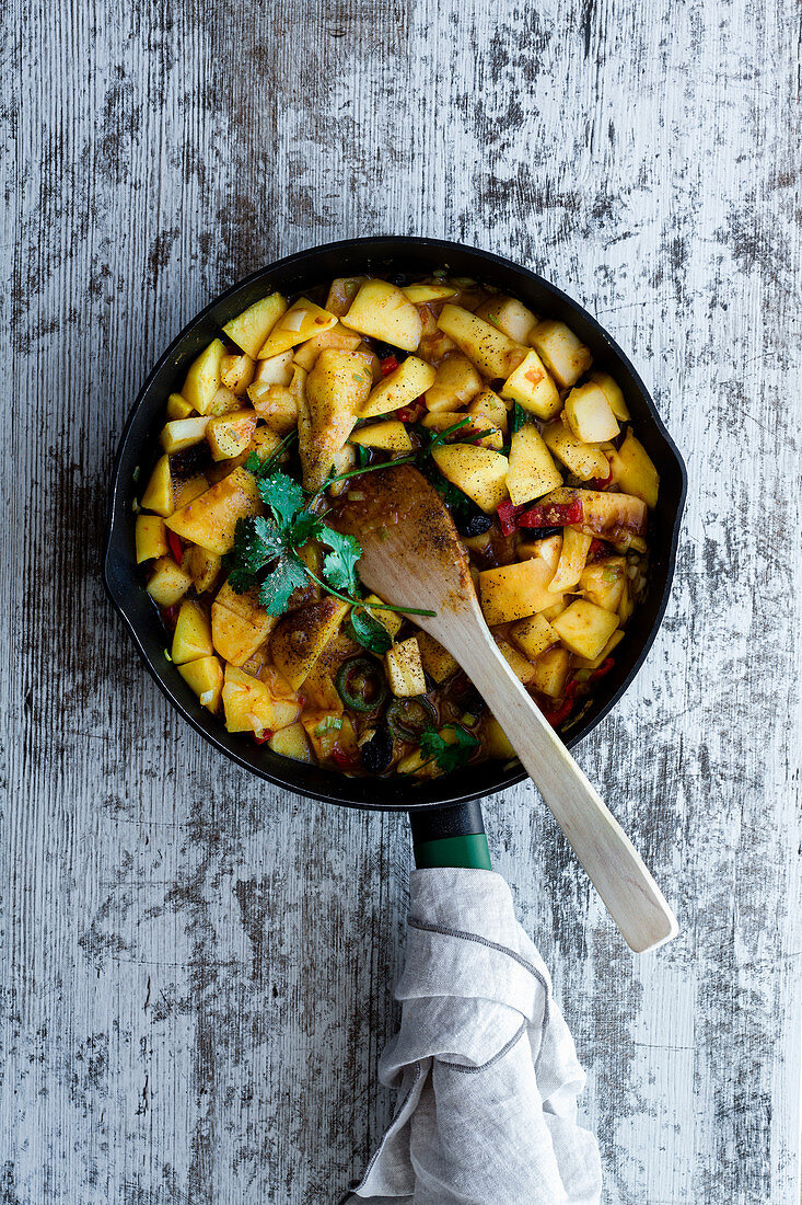 Sweet apples with onions and peppers with spices fried in pan