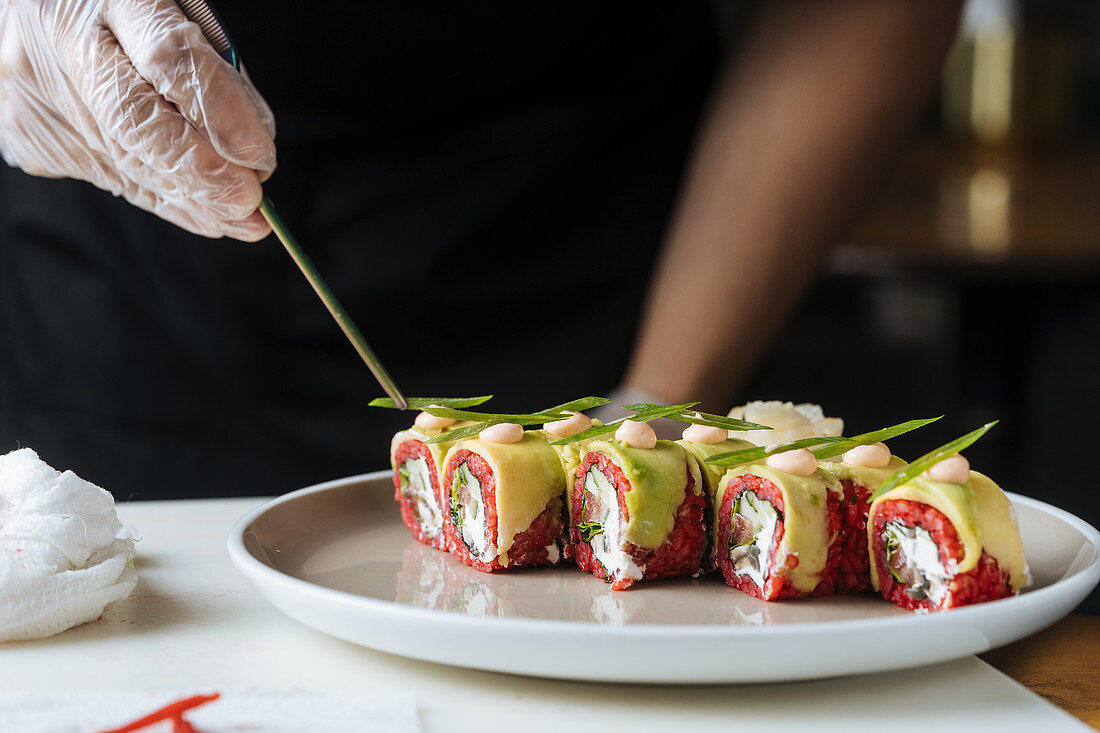 Cook in gloves decorating fresh tasty sushi with greens on white plate