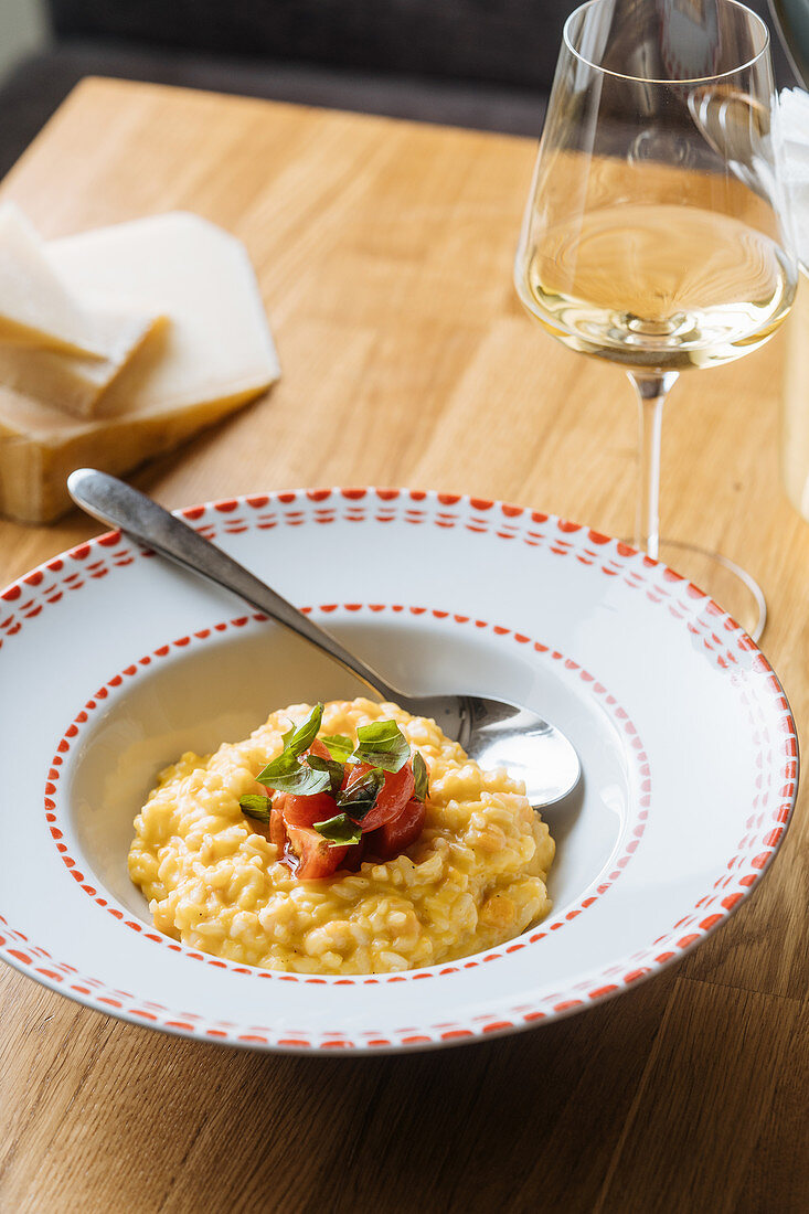 Appetizing risotto with pumpkin, sliced tomatoes and green
