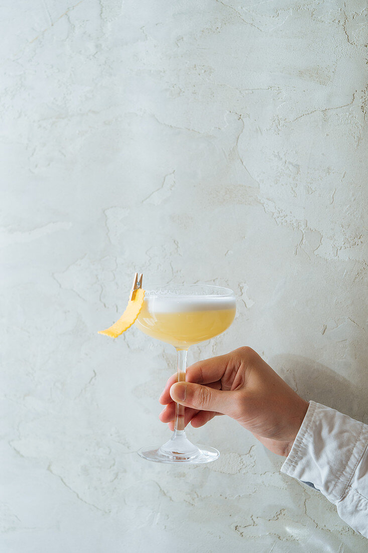 Cropped person holding fresh appetizing cocktail in glass festively decorated with clothespin