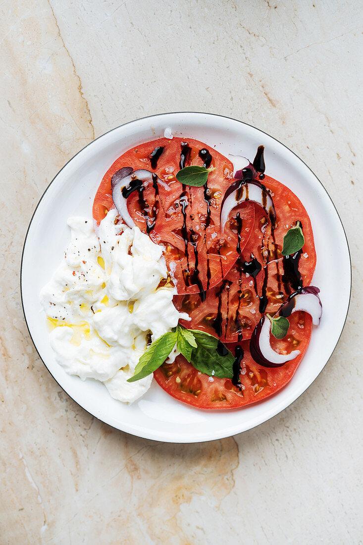 Tomato carpaccio with stacciatella, red onions and balsamic cream