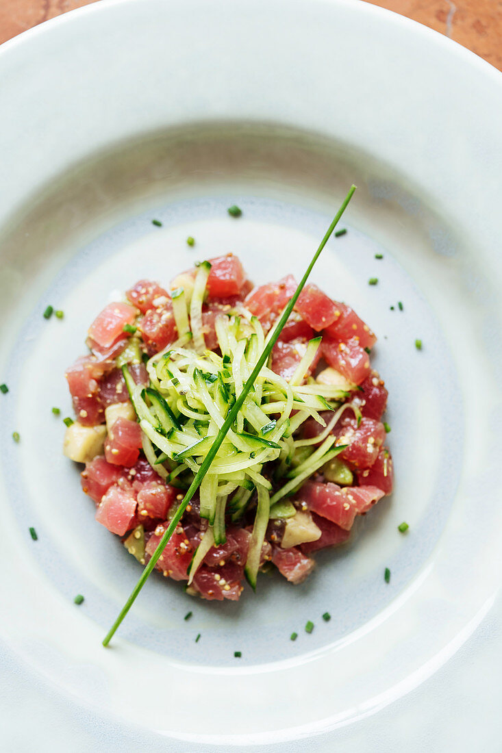 Pieces of red tuna served with slices of cucumber and herbs on white plate