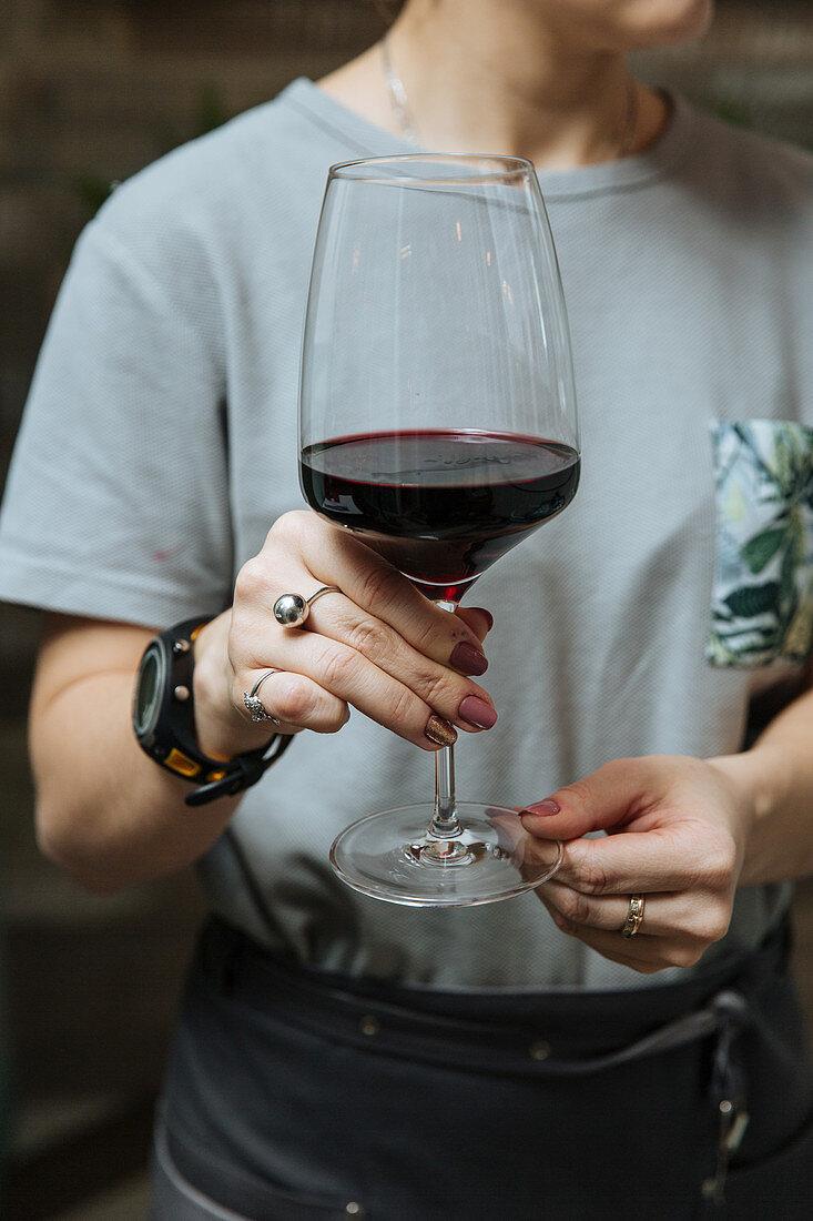 Kellnerin hält ein Glas Rotwein