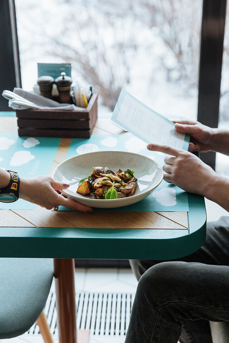 Waiter putting high cuisine dish on table while guest reading menu