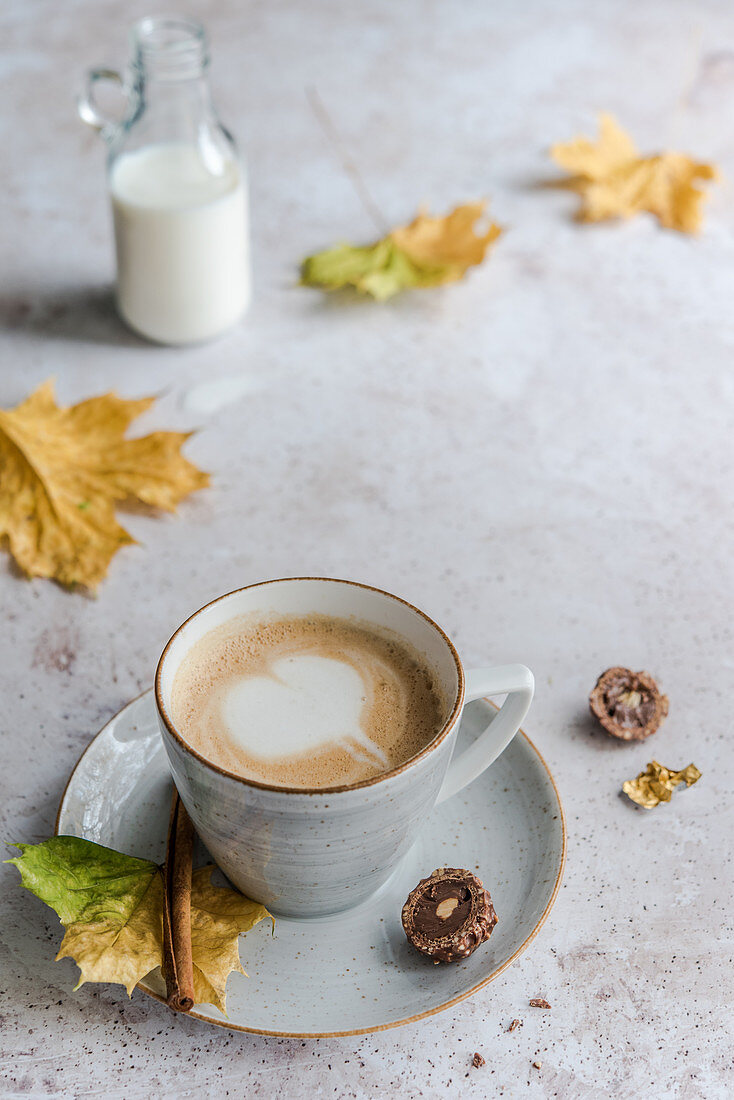 Cappuccino with a milk foam heart surrounded by autumn leaves