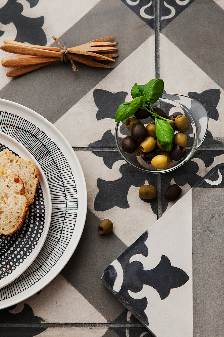 Bread, olive forks and bowl of olives on tiled surface with ornate pattern