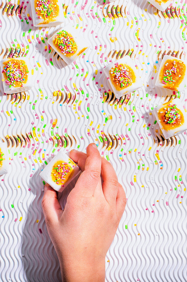 A child's hand reaches for a marshmallow with colorful sugar sprinkles