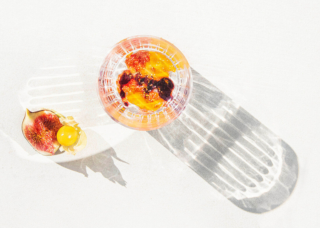Summer cocktail with fig and physalis puree in a glass casting a shadow