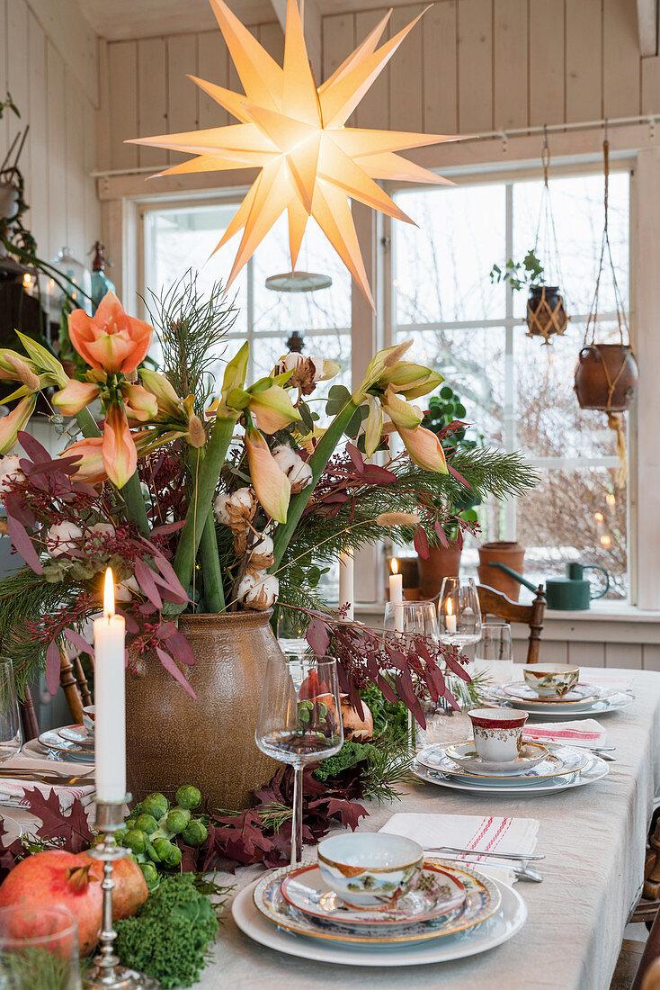 Lavish table centrepiece of amaryllis and leaves on set dinner table