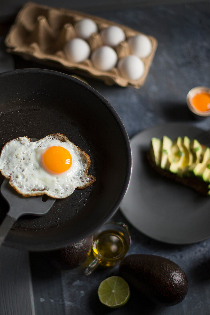 A fried egg in a pan served with fresh avocado for breakfast