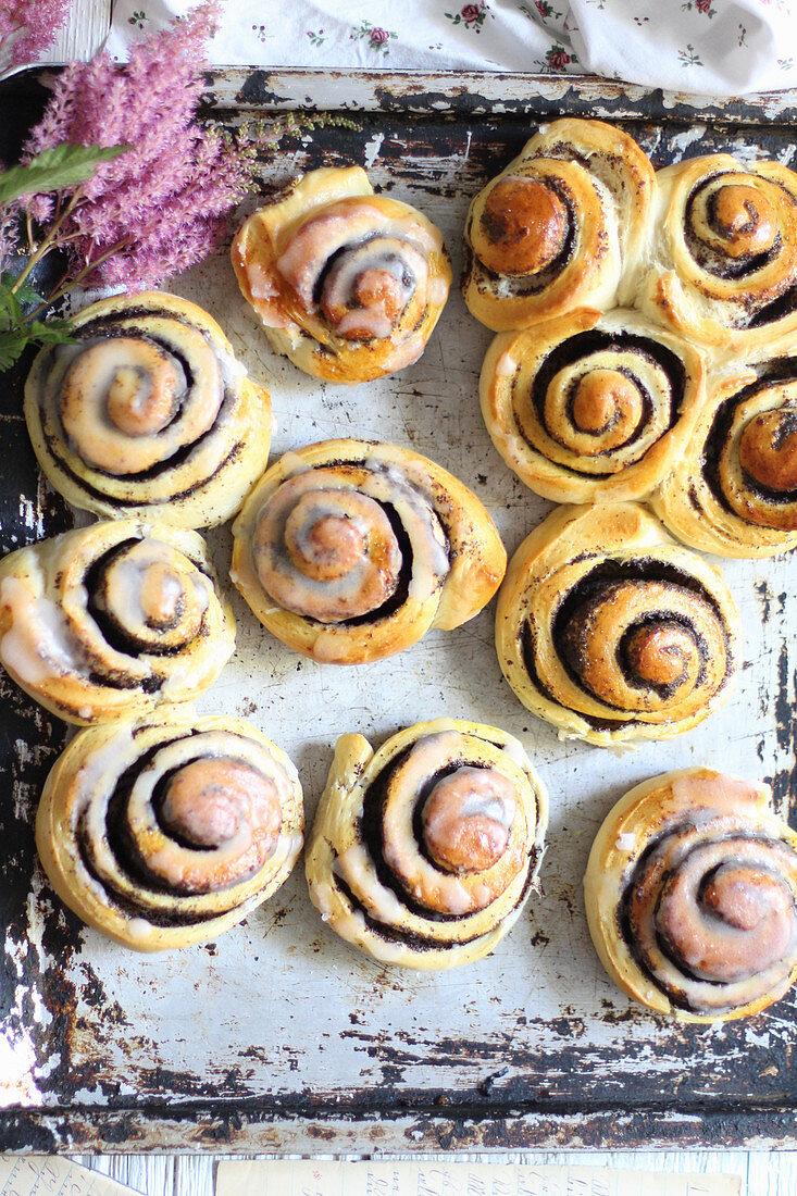 Glazed poppyseed buns on a backing tray