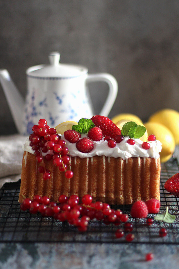 A loaf cake served with cream and summer berries