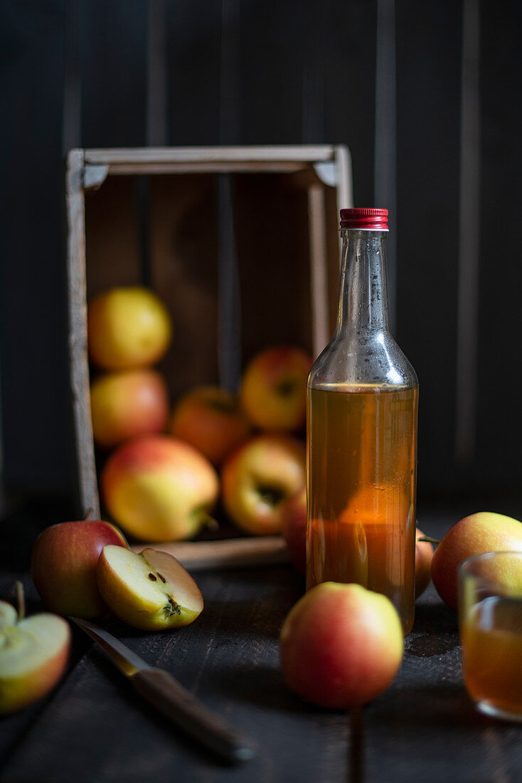 A bottle of cider with a wooden crate of apples in the background