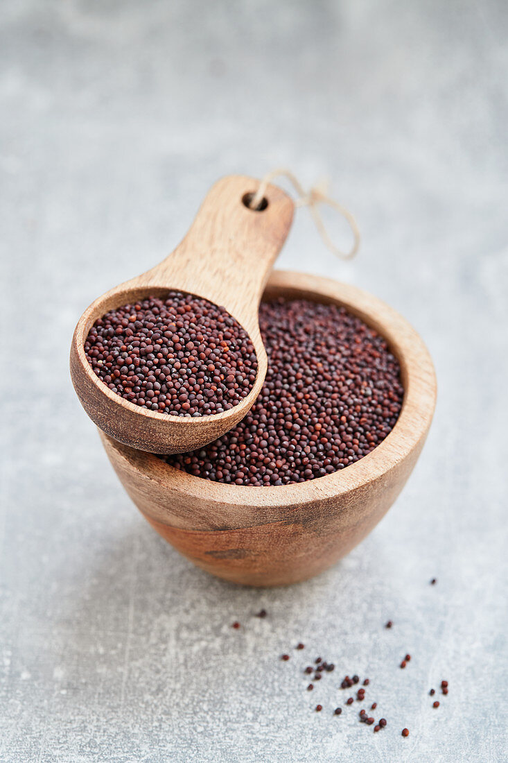 Broccoli seeds in a wooden bowl and a wooden scoop