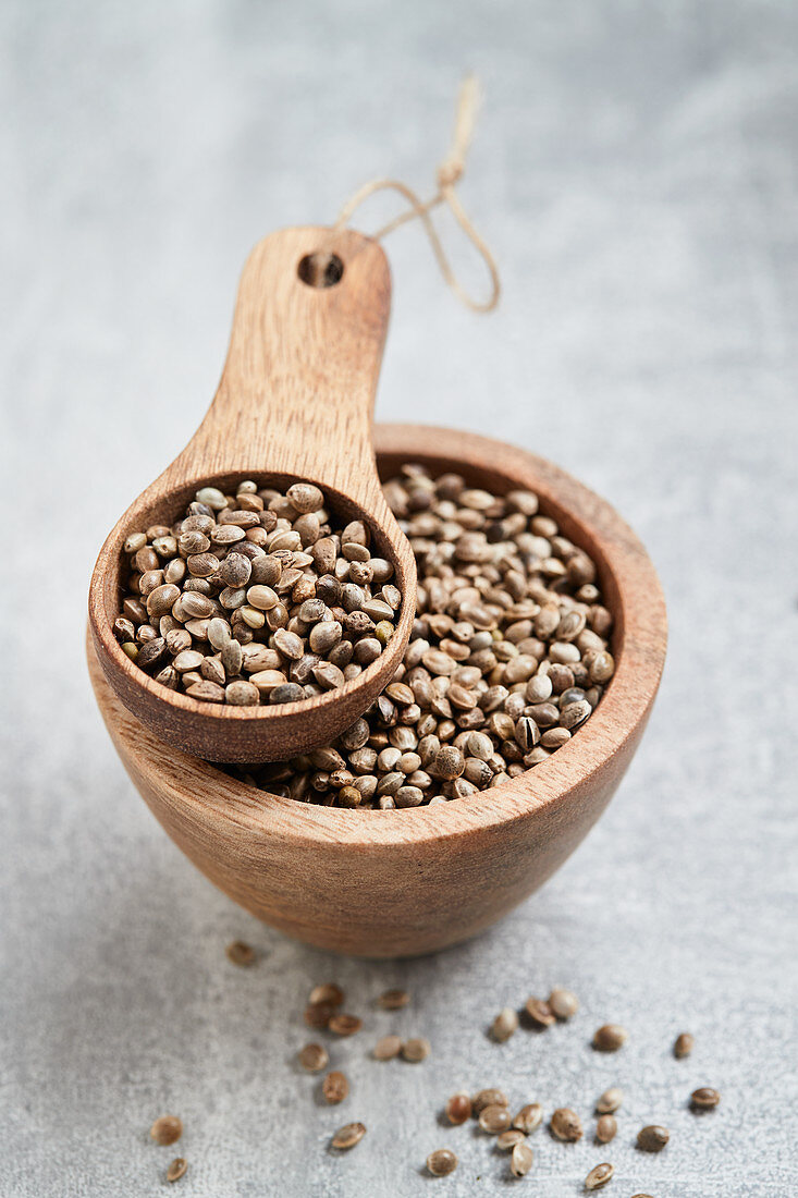 Hemp seeds in a wooden bowl and a wooden scoop