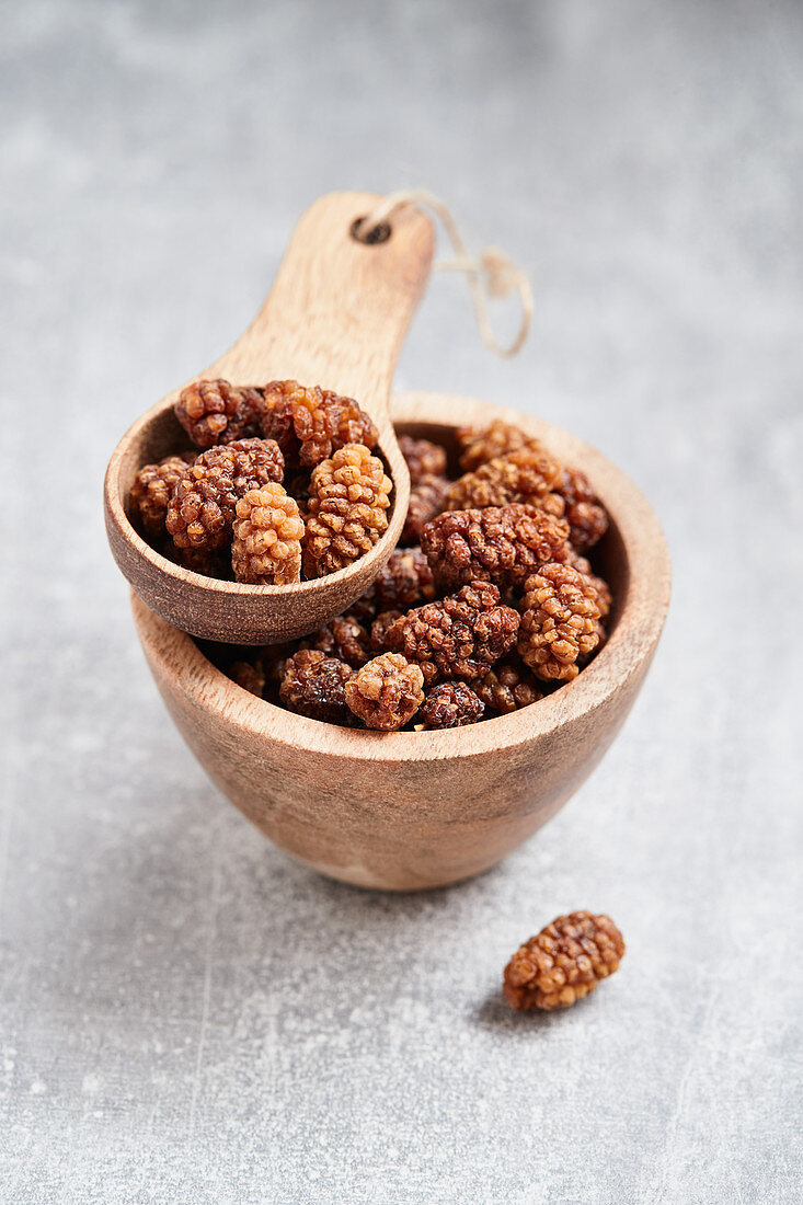 Mulberries in a wooden bowl and a wooden scoop