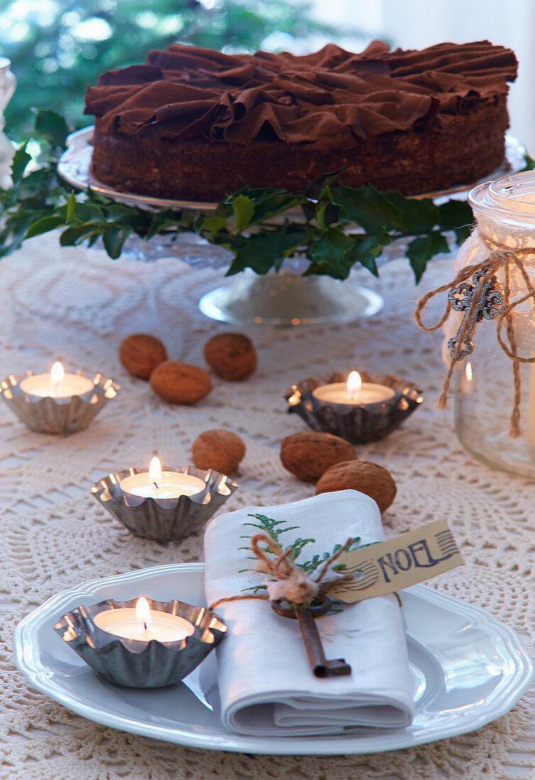 Chocolate torte and tealights in tiny flan tins on festively set table