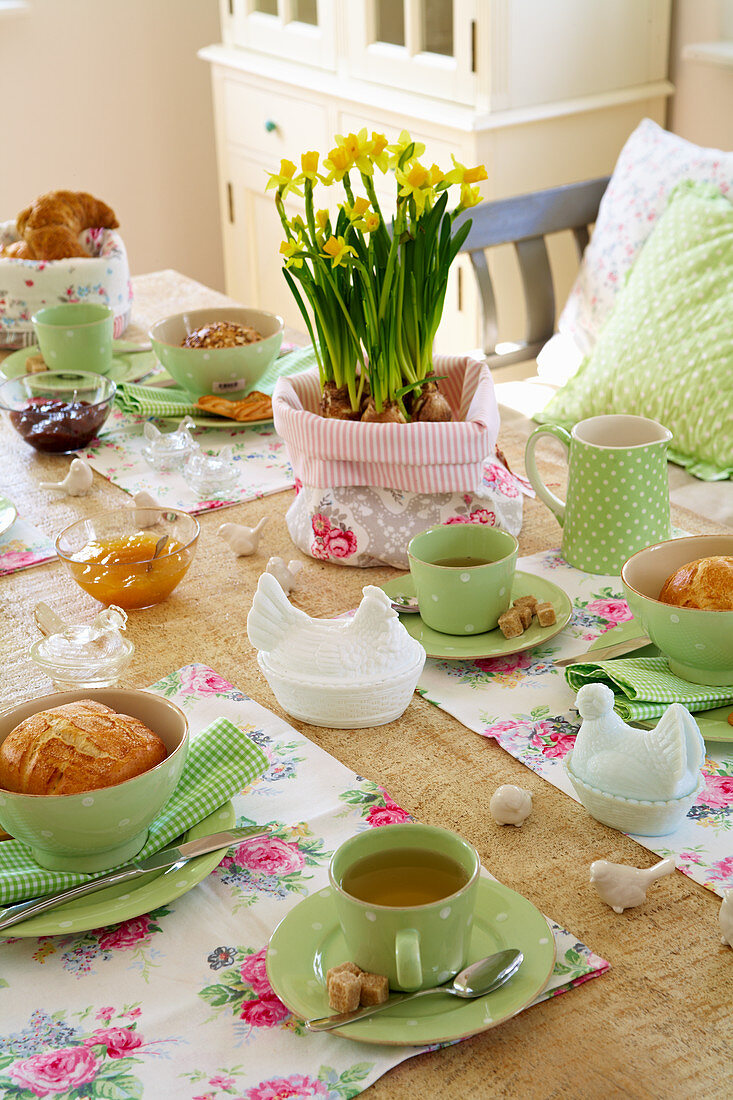Easter table prettily set with green crockery and floral placemats