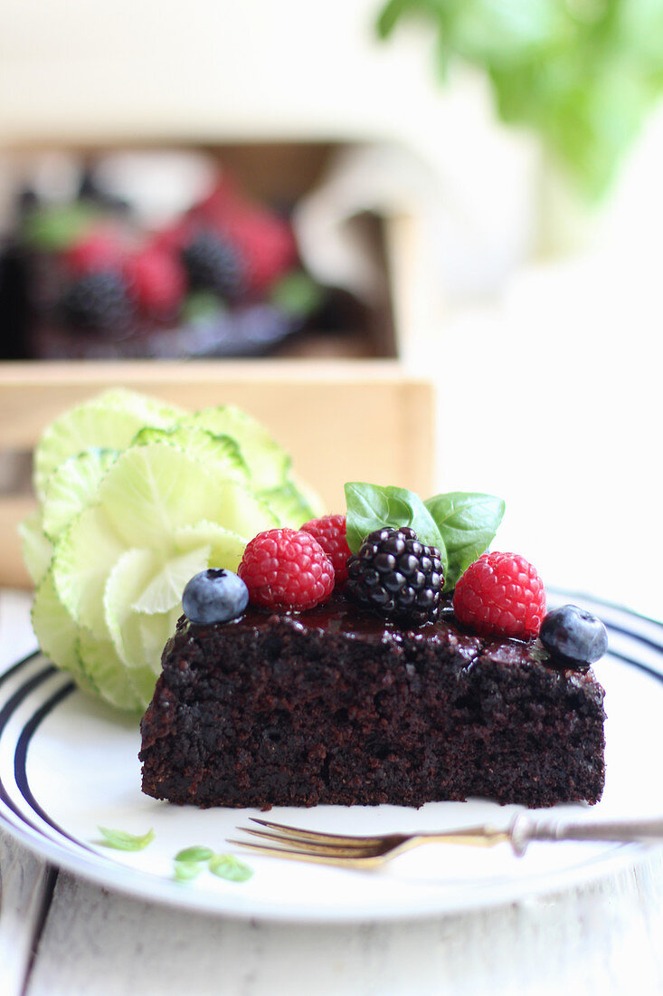 A slice of vegan chocolate cake with berries