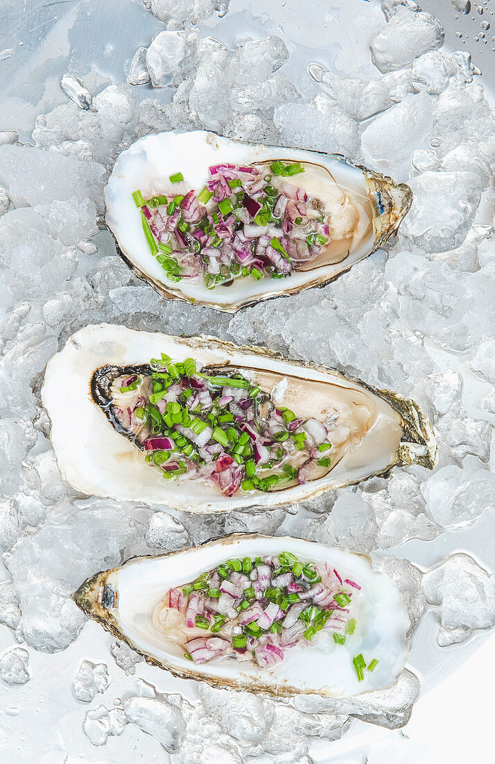 Opened oysters with chives and onions on ice