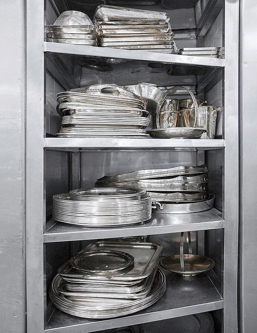 Metal kitchenware on a shelf in a commercial kitchen