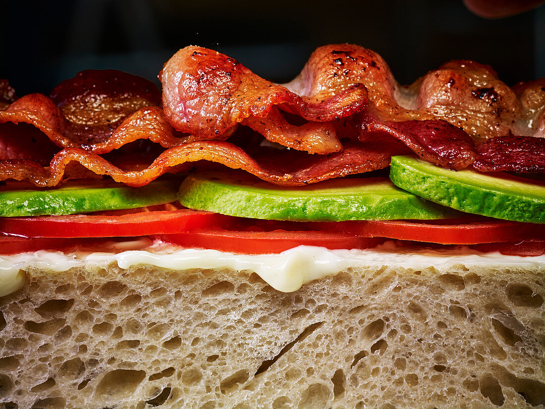 A bacon and salad sandwich on white bread