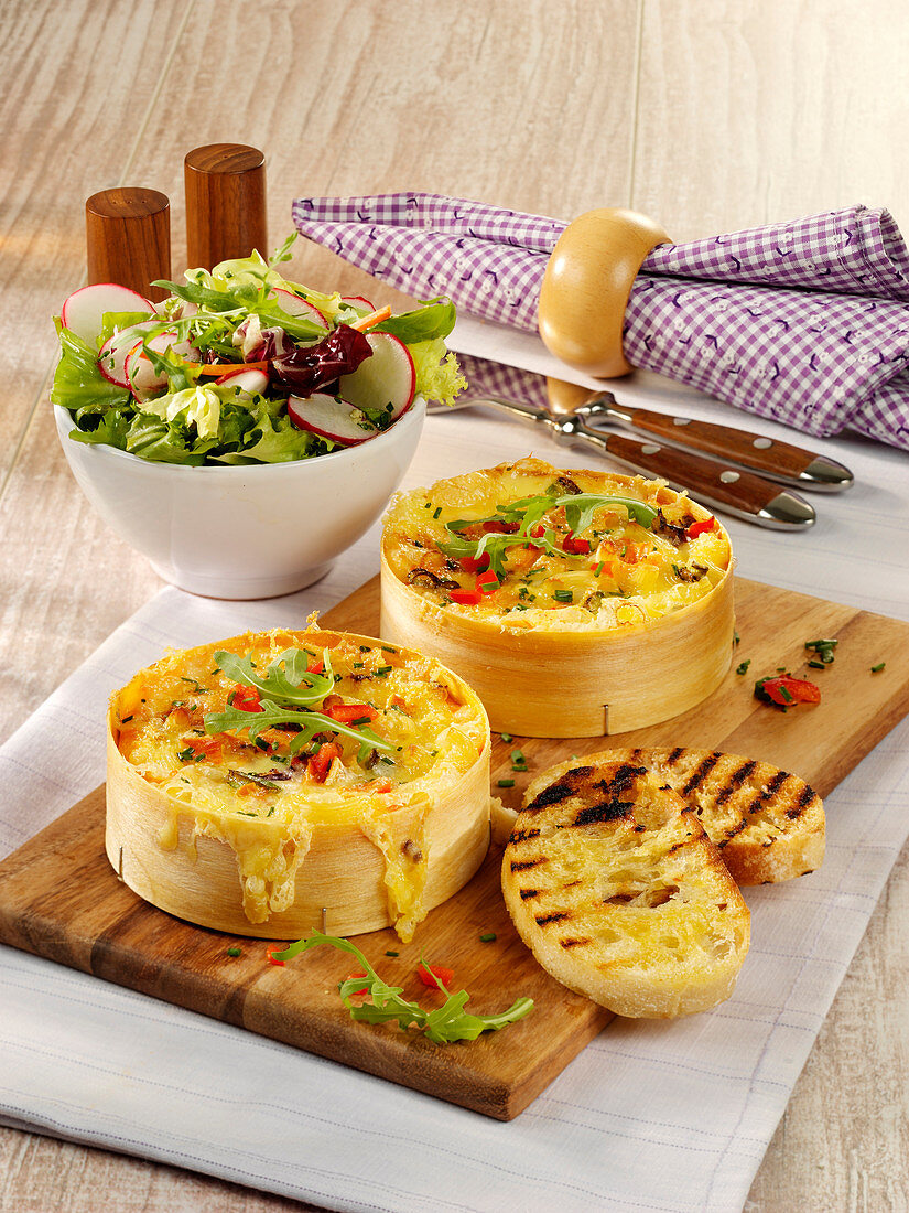 Pasta in cheese wheels with a crispy salad