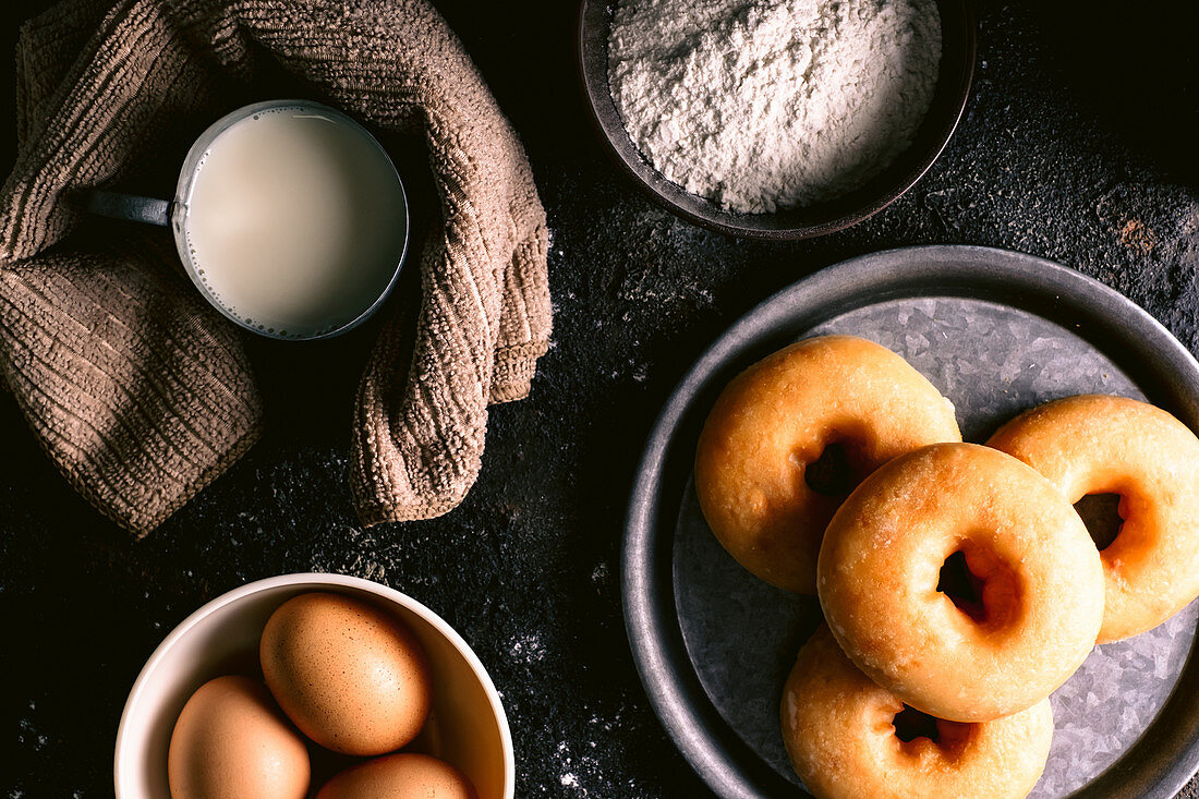 Doughnuts placed on rough table near various pastry ingredients and utensils