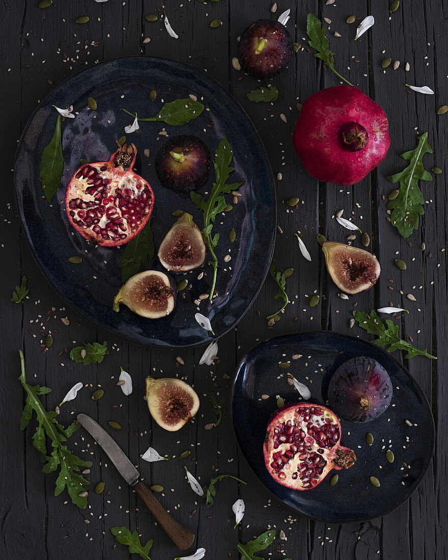 Fresh cut figs and pomegranates placed on plates near arugula and knife on lumber table