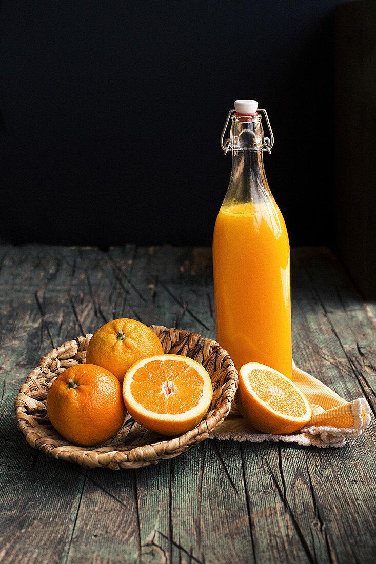 Bottle of fresh citric orange juice placed near halves of fresh oranges