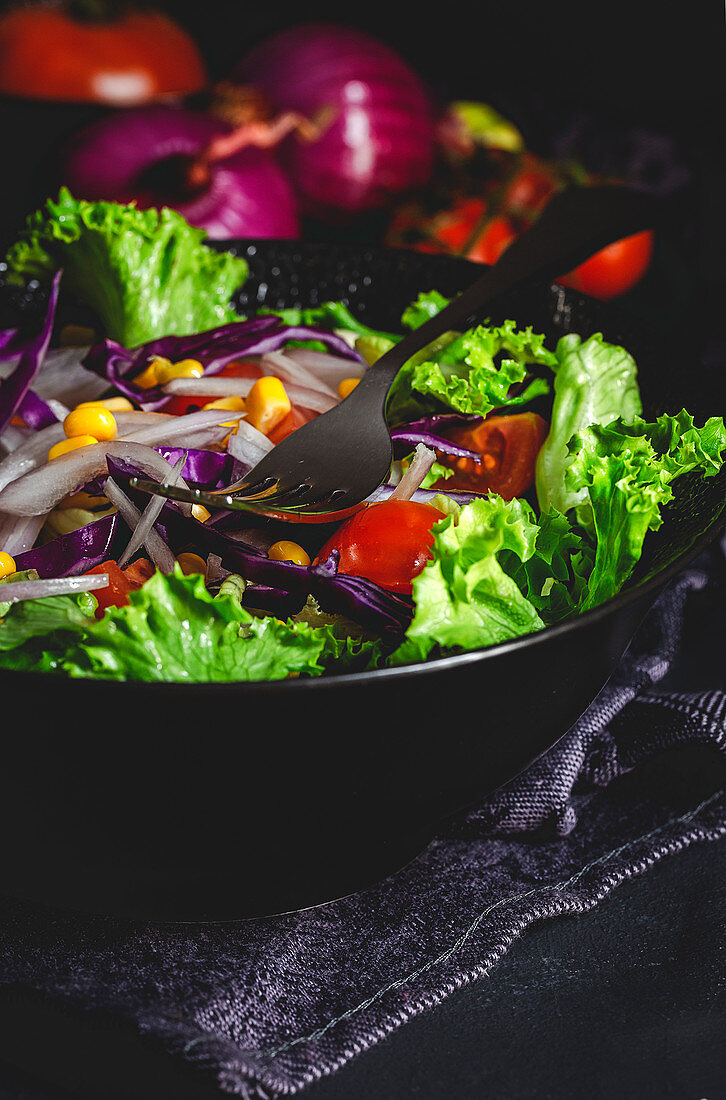 Healthy vegan food with fresh lettuce, cherries tomatoes, red onion and corn on dark background
