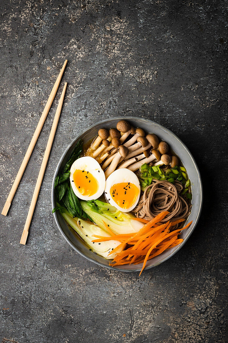 Miso soup with pak choy, carrot, soba pasta, mushrooms, egg and black sesame seeds