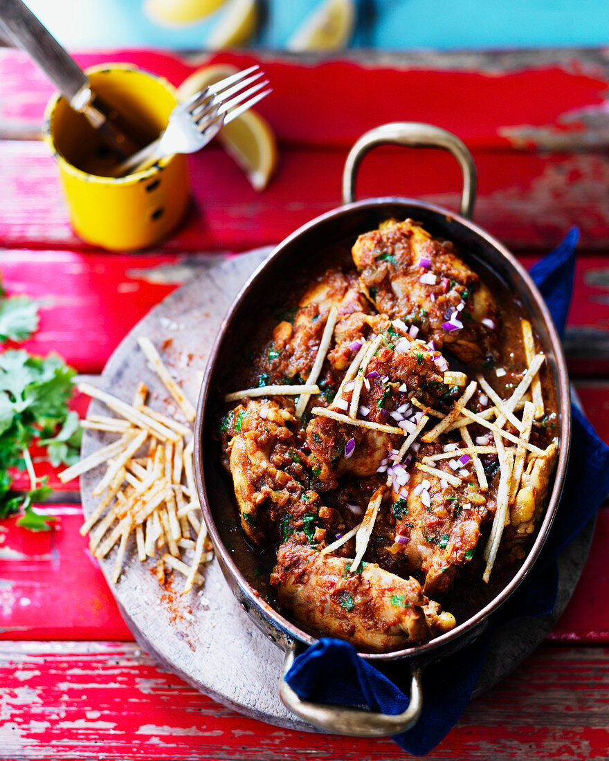 Lemon curry chicken with red onion, parsley and fries