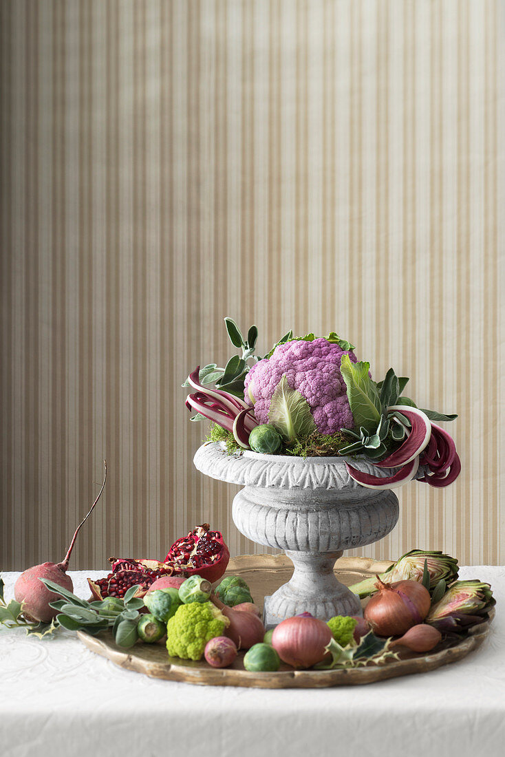 An arrangement of purple cauliflower, pomegranate seed and vegetables on a golden tray