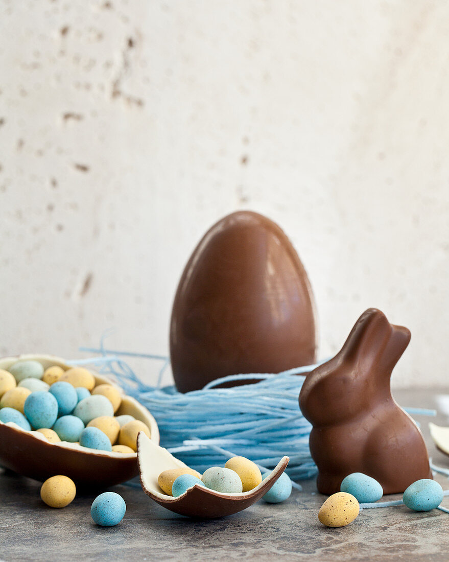 Easter chocolate egg in a blueberry candy nest, and a chocolate bunny, and a halved chocolate egg filled with mini chocolate eggs