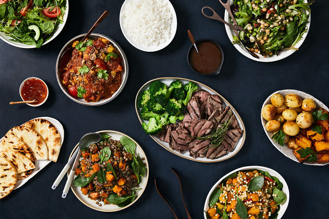 A lunch buffet with beef, vegetables, rice and salad