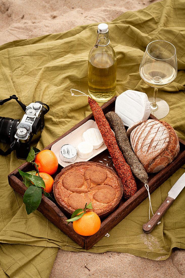 Holztablett mit Apfelpie, Käse, Salami, Brot und Früchten