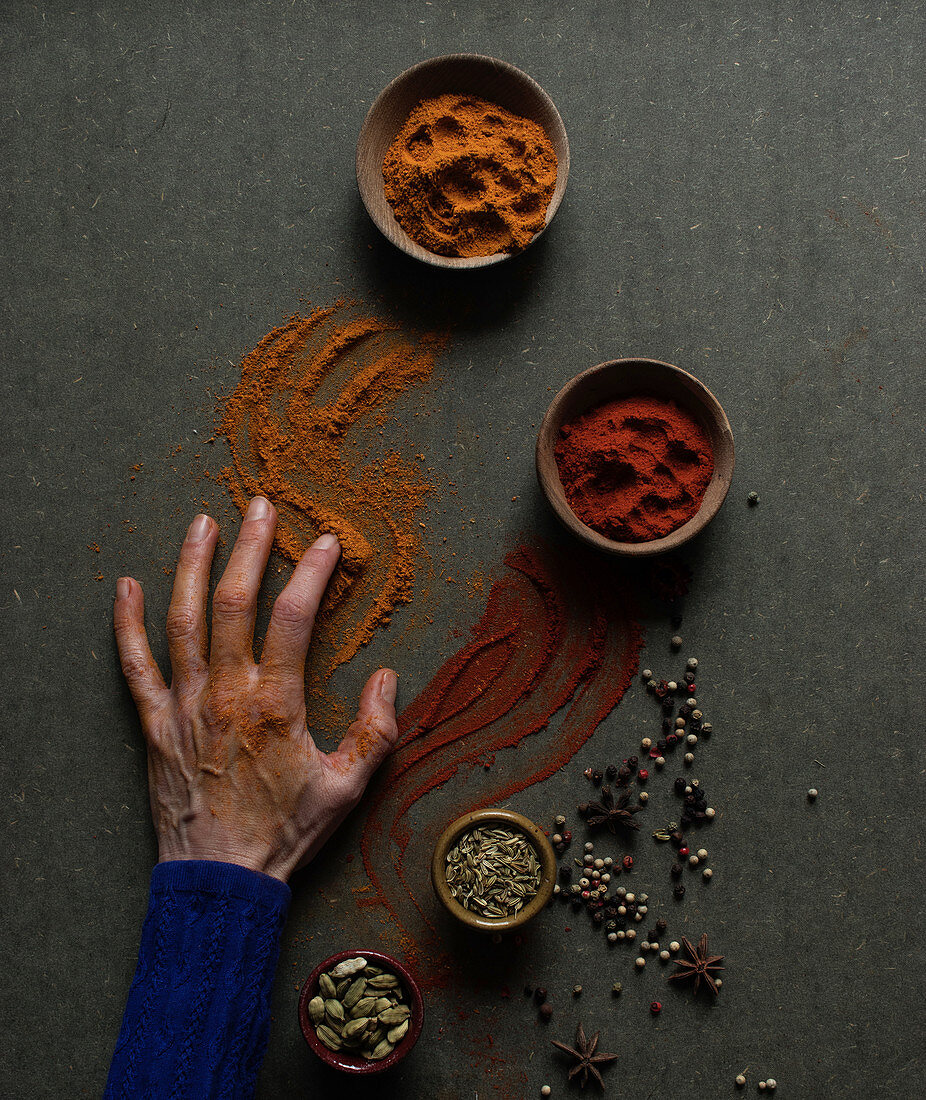Hand touching table with spilled paprika and cinnamon powders