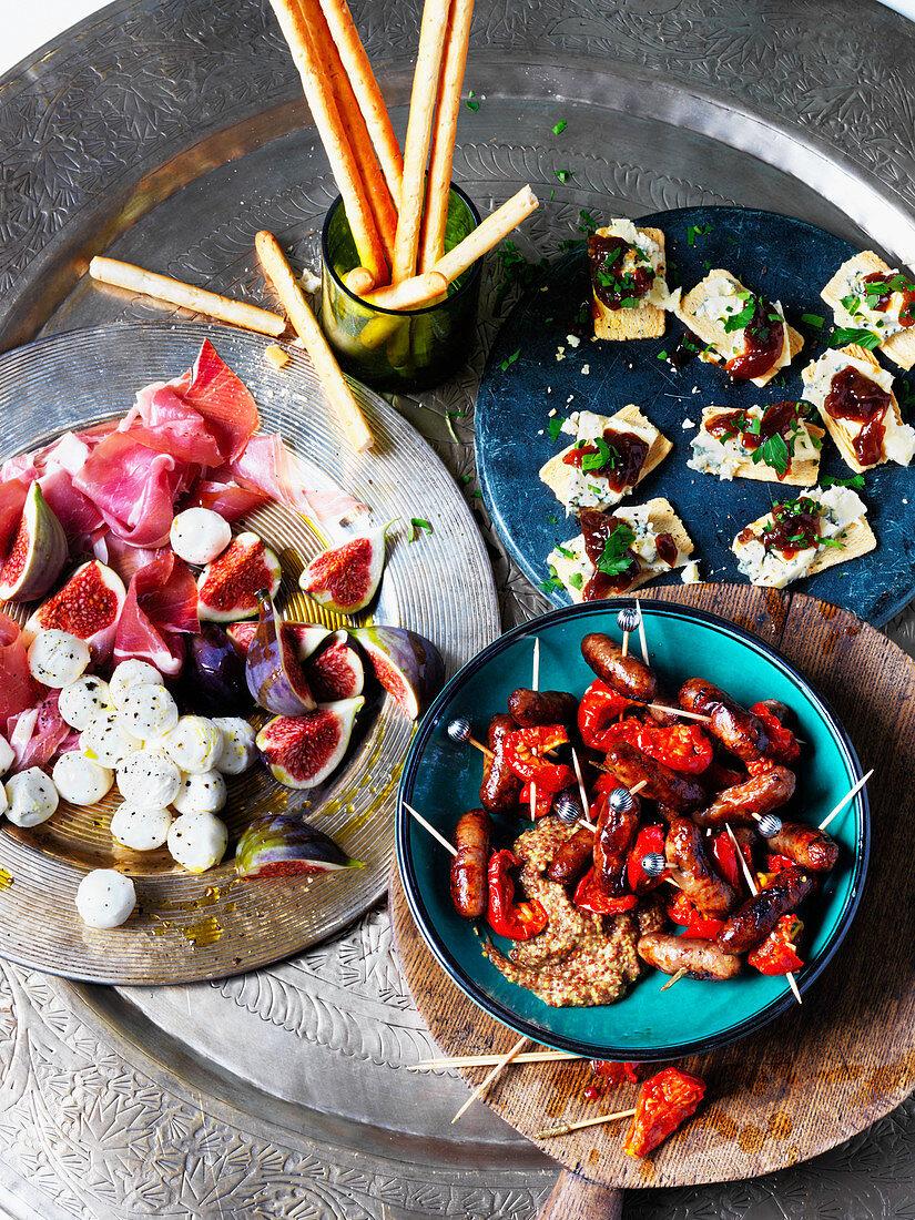 Party food: cocktail sausages, figs, mozarella balls, parma ham, chutney, stilton, breadsticks