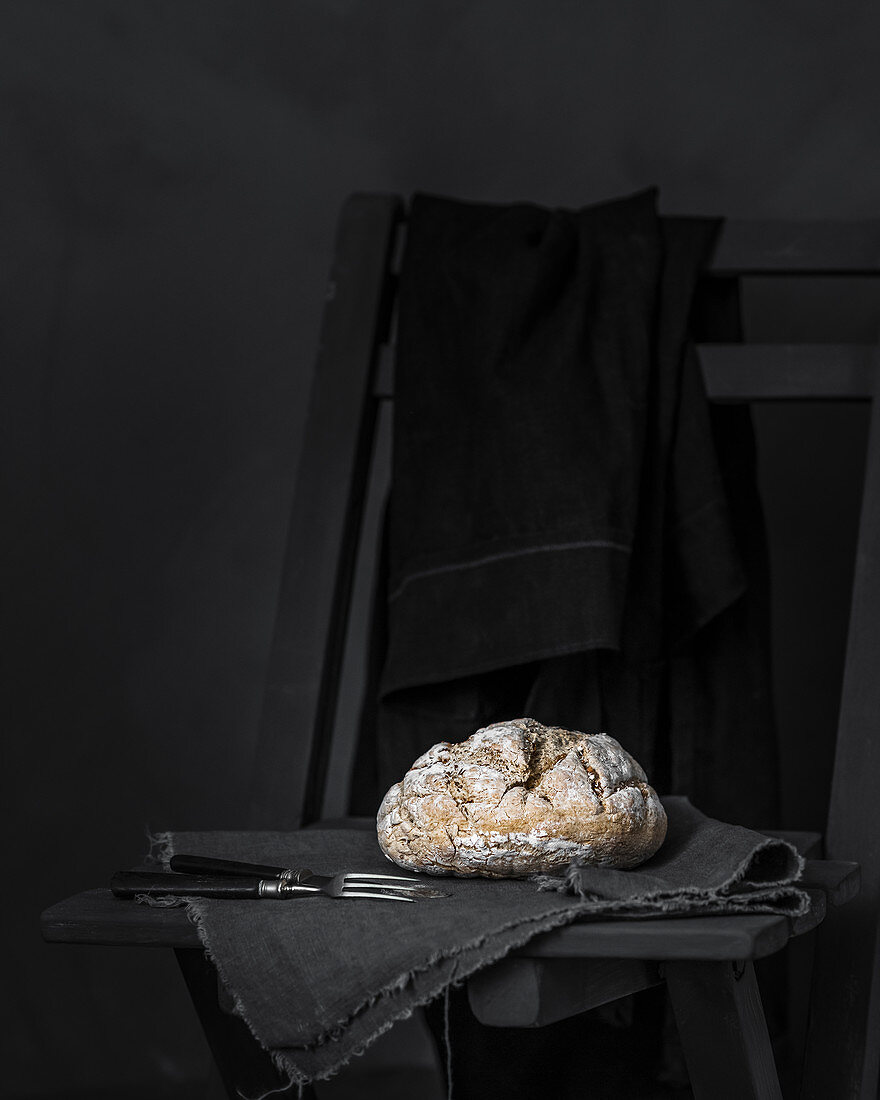 Homemade bread on linen against a black background