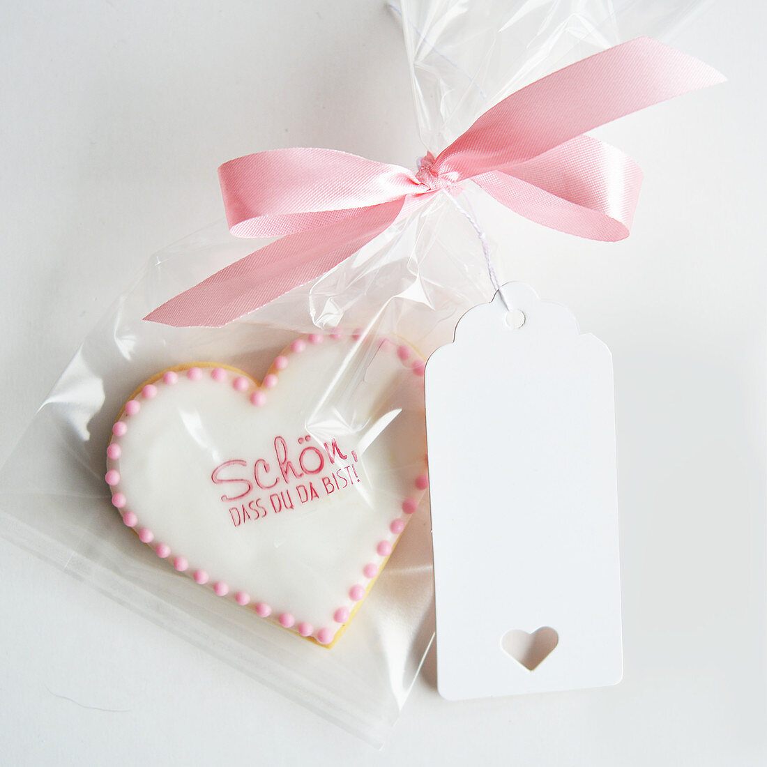 A biscuit with a saying packed in a cellophane bag with a pink bow