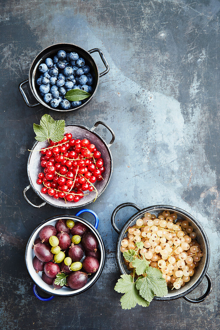 Various fresh berries in pots on a gray background