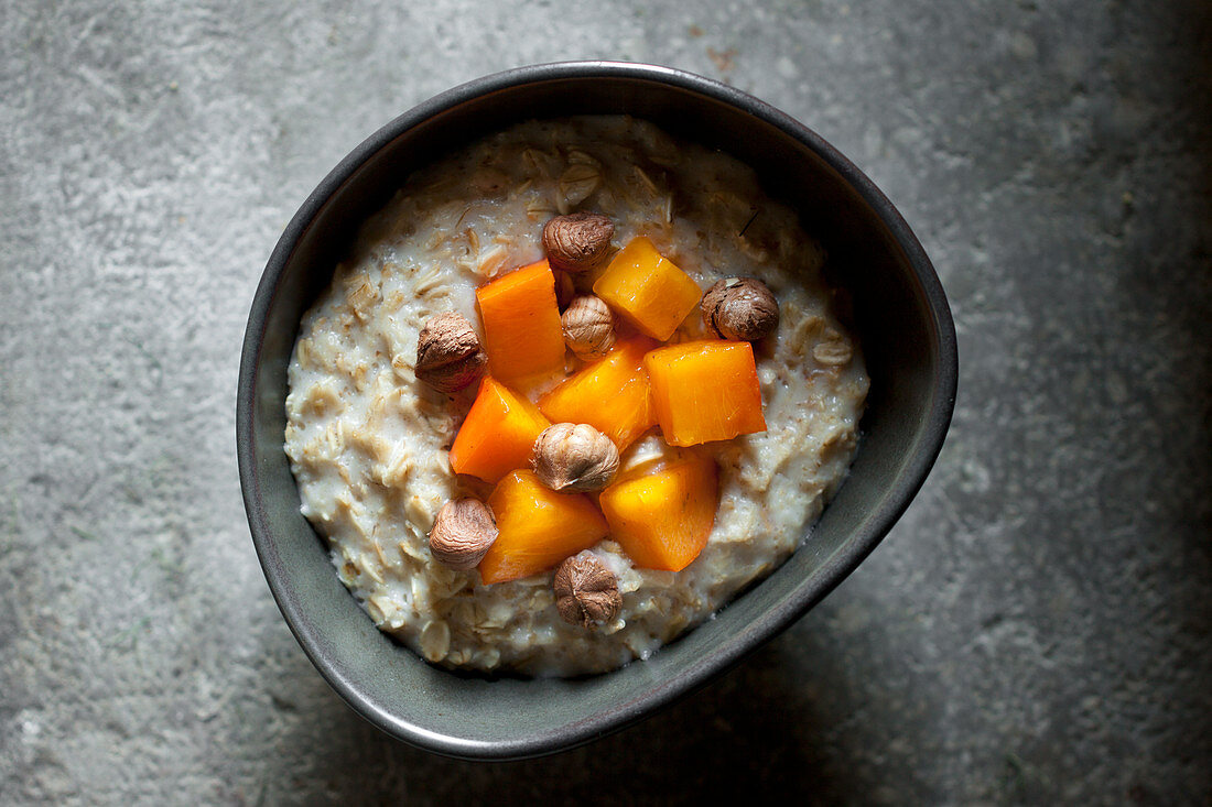 Whole rolled oat Porridge served with persimmon and hazelnuts